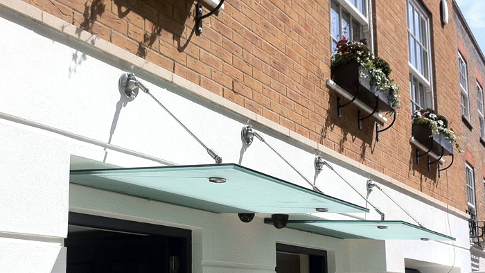 Custom made glass and stainless steel canopy for an entrance door.